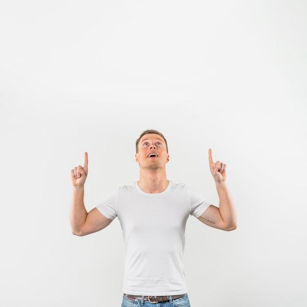 Retrato, de, um, sorrindo, homem jovem, dedos apontando, cima, olhar, contra, fundo branco Foto gratuita