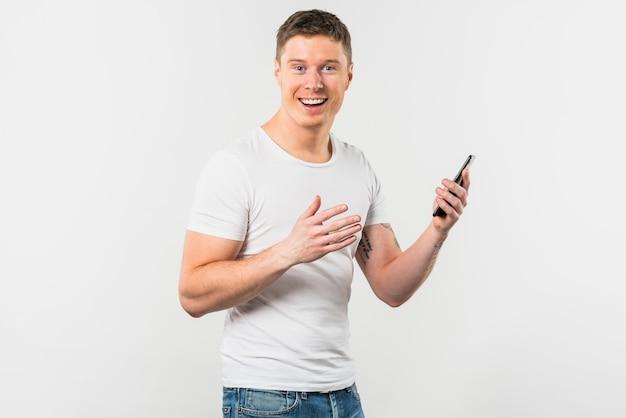 Retrato, de, um, sorrindo, homem jovem, segurando, telefone móvel, em, mão, olhando câmera Foto gratuita