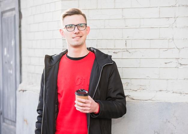 Retrato, de, um, sorrindo, homem jovem, xícara takeaway, xícara de café, olhando Foto gratuita