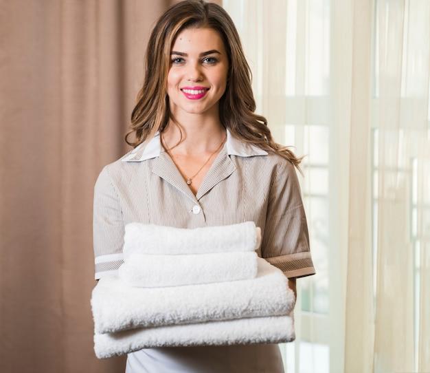 Retrato, de, um, sorrindo, hotel, empregada, em, sala, segurando, pilha, de, branca, toalhas Foto gratuita