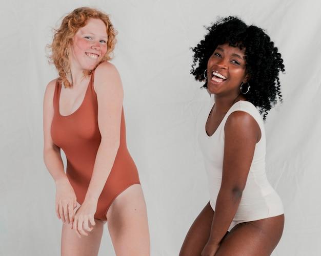 Retrato, de, um, sorrindo, jovem, africano, e, loiro, mulheres, contra, cinzento, fundo Foto gratuita