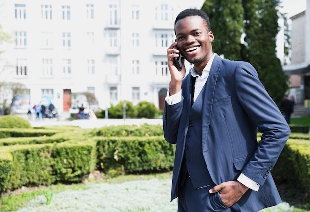 Retrato, de, um, sorrindo, jovem, africano, homem negócios, falando telefone móvel Foto gratuita