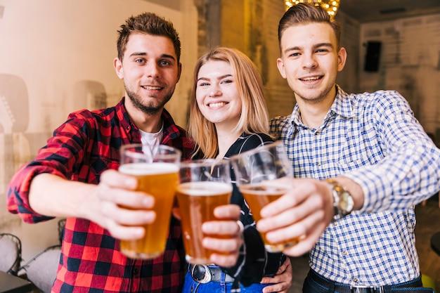 Retrato, de, um, sorrindo, jovem, amigos, brindar, a, copos cerveja Foto gratuita