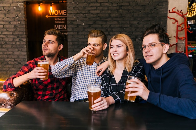 Retrato, de, um, sorrindo, jovem, amigos, desfrutando, a, cerveja Foto gratuita