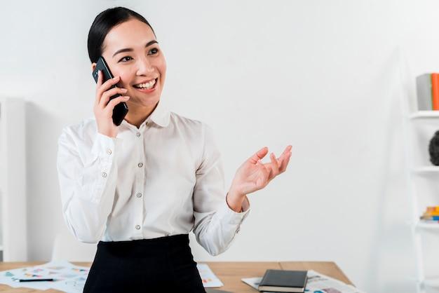 Retrato, de, um, sorrindo, jovem, executiva, conversa telefone móvel, em, escritório Foto gratuita