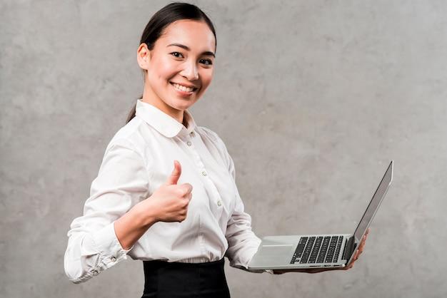 Retrato, de, um, sorrindo, jovem, executiva, segurando, laptop, em, mão, mostrando, polegar, sinal Foto gratuita