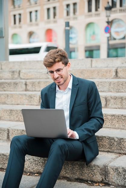 Retrato, de, um, sorrindo, jovem, homem negócios, sentar escada, usando computador portátil Foto gratuita