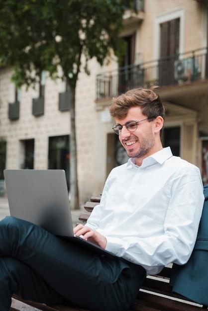 Retrato, de, um, sorrindo, jovem, homem negócios, usando computador portátil Foto gratuita