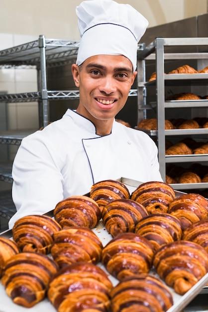 Retrato, de, um, sorrindo, jovem, macho, padeiro, segurando, fresco, bandeja croissant Foto gratuita
