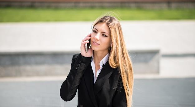 Retrato, de, um, sorrindo, jovem, mulher negócio, conversa telefone Foto Premium