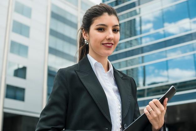 Retrato, de, um, sorrindo, jovem, mulher negócios fica, frente, predios Foto gratuita