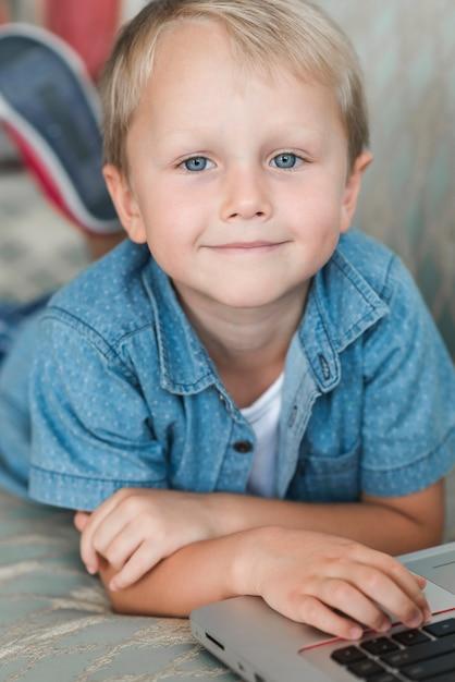 Retrato, de, um, sorrindo, loiro, menino, com, laptop Foto gratuita