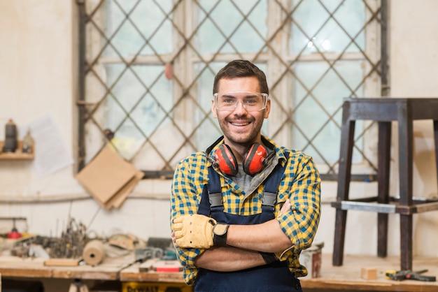 Retrato, de, um, sorrindo, macho, carpinteiro, ficar, frente, workbench Foto gratuita