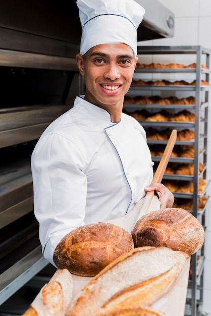 Retrato, de, um, sorrindo, macho jovem, padeiro, mostrando, freshly, assado, pão, ligado, madeira, pá Foto gratuita