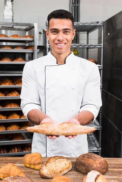 Retrato, de, um, sorrindo, macho jovem, padeiro, segurando, pão baguette Foto gratuita