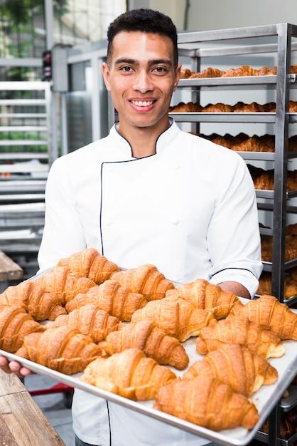 Retrato, de, um, sorrindo, macho, padeiro, segurando bandeja, de, croissant cozido Foto gratuita