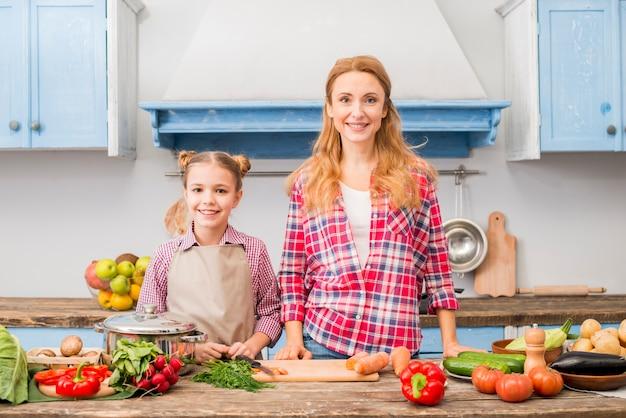 Retrato, de, um, sorrindo, mãe, e, dela, filha, ficar, frente, tabela, com, legumes Foto gratuita