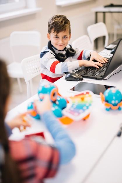 Retrato, de, um, sorrindo, menino, com, laptop, escrivaninha, olhando câmera Foto gratuita