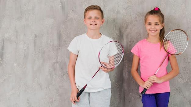 Retrato, de, um, sorrindo, menino menina, segurando, raquete, em, mãos, contra, parede concreta Foto gratuita
