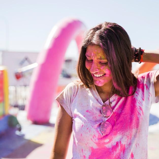 Retrato, de, um, sorrindo, mulher jovem, coberto, com, cor holi cor-de-rosa Foto gratuita