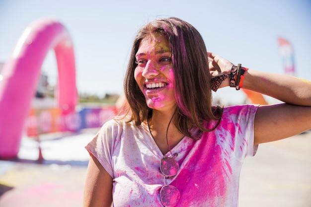 Retrato, de, um, sorrindo, mulher jovem, com, holi, cor, rosto Foto gratuita