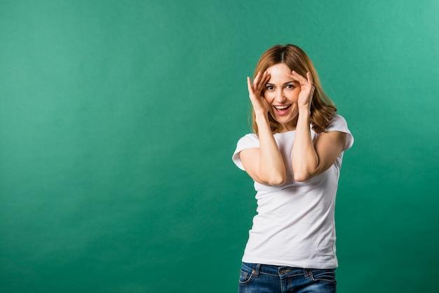 Retrato, de, um, sorrindo, mulher jovem, contra, verde, fundo Foto gratuita