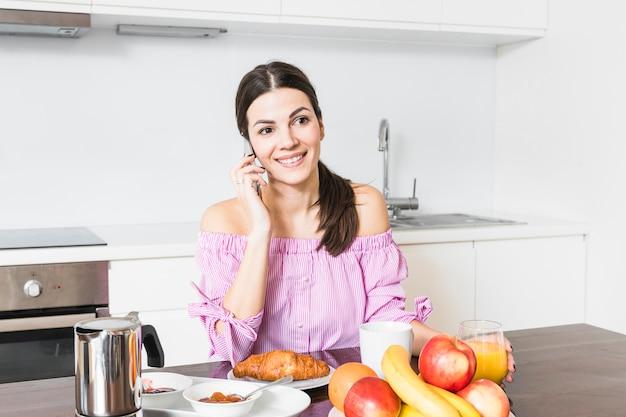 Retrato, de, um, sorrindo, mulher jovem, falando telefone móvel, tendo, pequeno almoço Foto gratuita