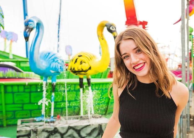 Retrato, de, um, sorrindo, mulher jovem, ficar, frente, chafariz Foto gratuita