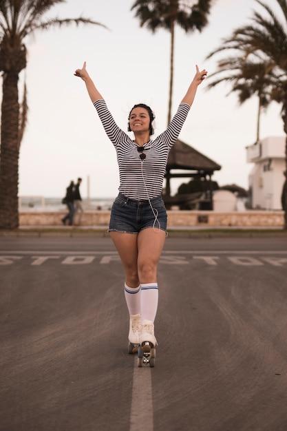 Retrato, de, um, sorrindo, mulher jovem, ficar, ligado, estrada, levantamento, dela, mãos, escutar música, ligado, headphone Foto gratuita