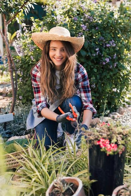 Retrato, de, um, sorrindo, mulher jovem, podar, a, plantas, olhando câmera Foto gratuita