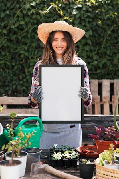 Retrato, de, um, sorrindo, mulher jovem, segurando, em branco branco, quadro, em, mão Foto gratuita