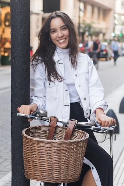 Retrato, de, um, sorrindo, mulher jovem, sentando, ligado, bicicleta, em, rua Foto gratuita