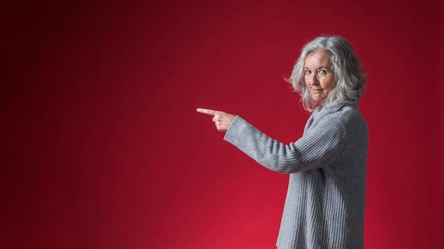 Retrato, de, um, sorrindo, mulher sênior, apontar, dela, dedo, contra, vermelho, fundo Foto gratuita