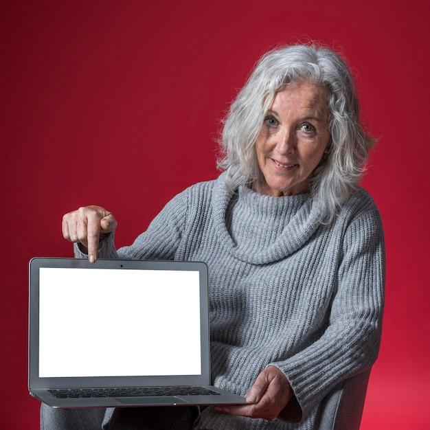 Retrato, de, um, sorrindo, mulher sênior, apontar, dela, dedo, ligado, laptop, contra, vermelho, fundo Foto gratuita