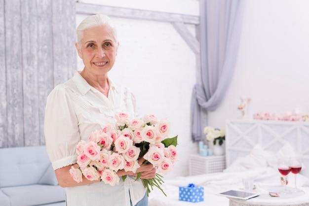 Retrato, de, um, sorrindo, mulher sênior, segurando, buquê, de, rosa, flores, casa Foto gratuita