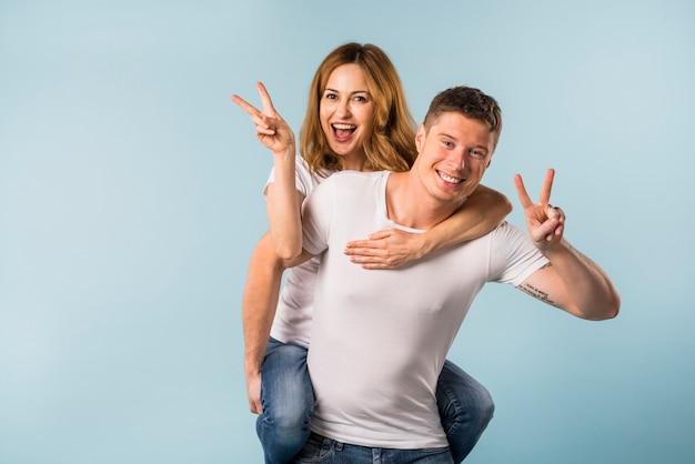 Retrato, de, um, sorrindo, namorada, montando, ligado, seu, namorado, costas, mostrando, sinal vitória Foto gratuita