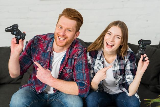 Retrato, de, um, sorrindo, par jovem, apontar dedo, direção, a, video game, controlador Foto gratuita