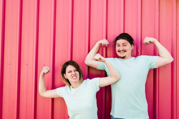 Retrato, de, um, sorrindo, par jovem, flexionar, seu, braços, contra, corrugado, ferro, folha Foto gratuita