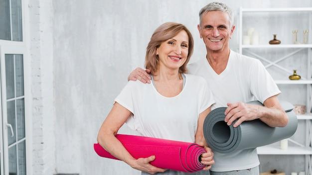 Retrato, de, um, sorrindo, par velho, em, sportswear, carregar, tapetes ioga Foto gratuita