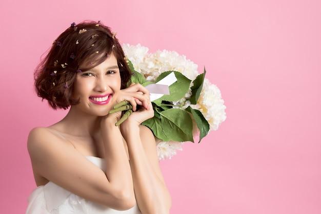 Retrato, de, um, sorrindo, playful, cute, mulher segura, flores, isolado, ligado, cor-de-rosa Foto gratuita