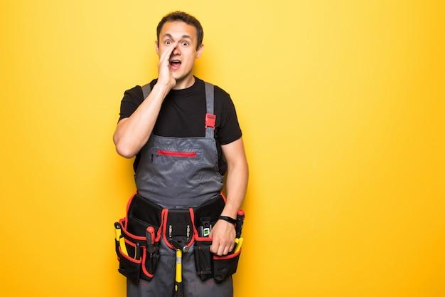 Retrato de um técnico gritando enquanto mantém os fios contra o fundo amarelo Foto Premium