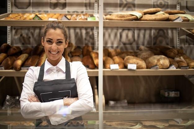 Retrato de um vendedor de padaria com os braços cruzados em frente a uma prateleira cheia de pães e doces caseiros Foto gratuita