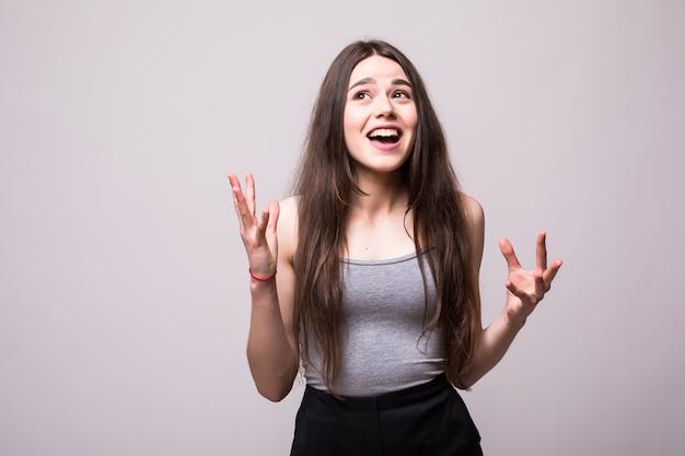 Retrato de uma adolescente alegre e feliz, vestida com uma jaqueta jeans, comemorando o sucesso enquanto dança isolada Foto gratuita