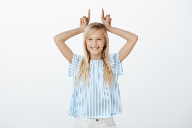 Retrato de uma adorável garotinha brincalhona de cabelo loiro, se divertindo enquanto zomba, segurando o dedo indicador acima da cabeça como se estivesse mostrando chifres, sorrindo alegremente por cima da parede cinza Foto gratuita