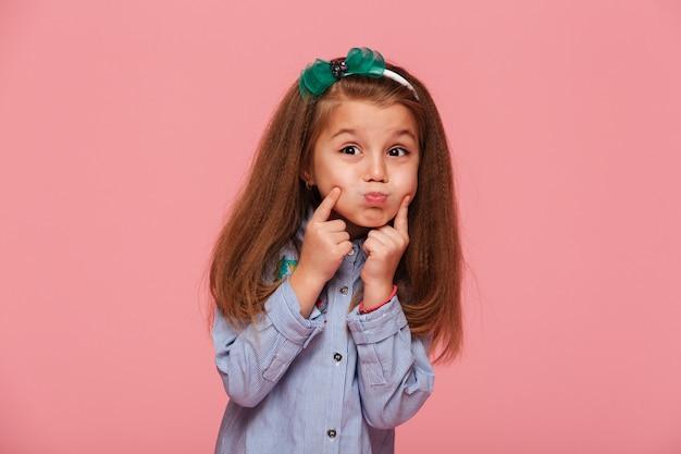 Retrato de uma adorável menina com cabelo ruivo longo bonito, explodindo suas bochechas, tocando o rosto Foto gratuita