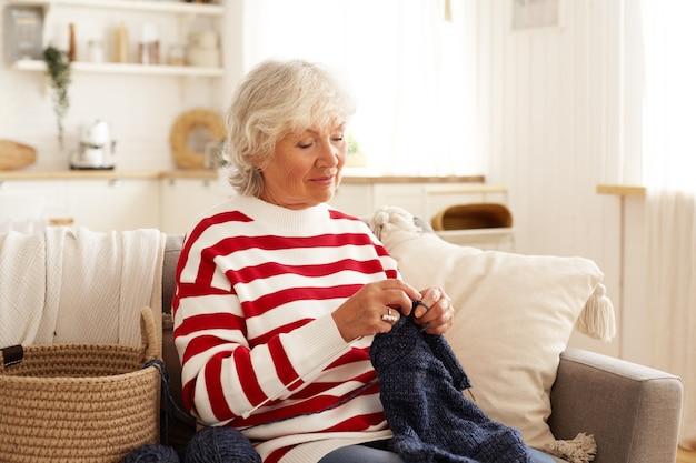Retrato de uma aposentada feminina de cabelos grisalhos concentrada em roupas casuais, passando o tempo suéter de tricô sentado contra o aconchegante quarto interior Foto gratuita