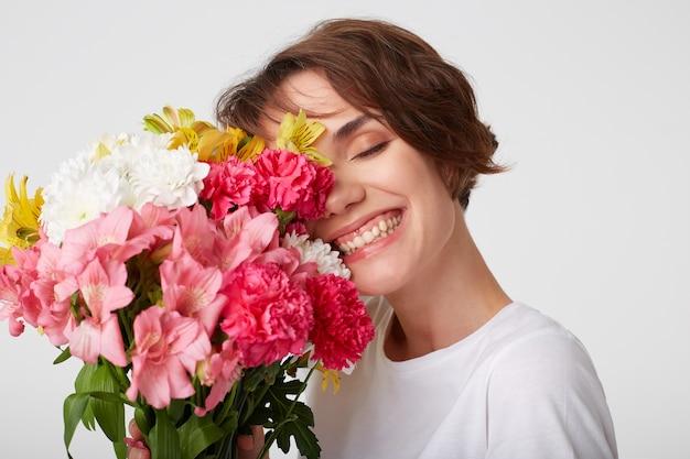 Retrato de uma bela garota de cabelos curtos em t-shirt branca em branco, segurando um buquê, cobre o rosto com flores, em pé sobre um fundo branco com os olhos fechados. Foto gratuita