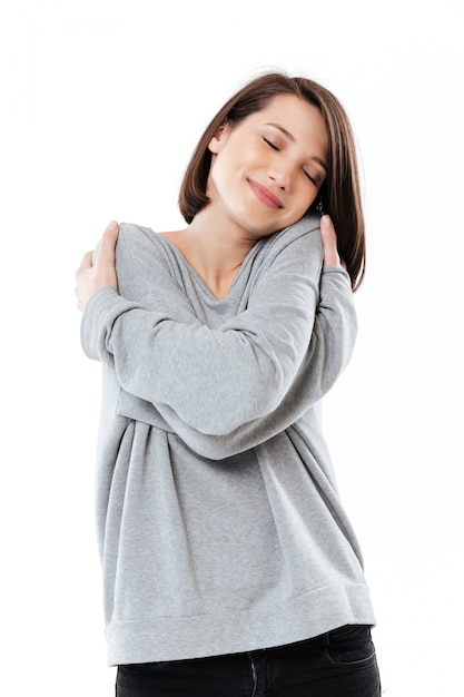 Retrato de uma bela jovem, abraçando-se em pé Foto gratuita