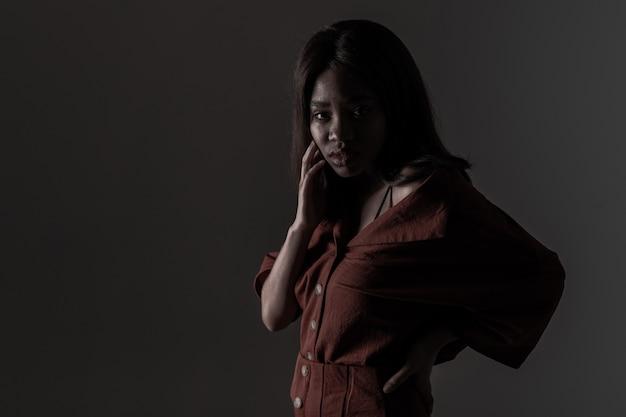 Retrato de uma bela jovem africana natural possing sobre fundo preto Foto Premium