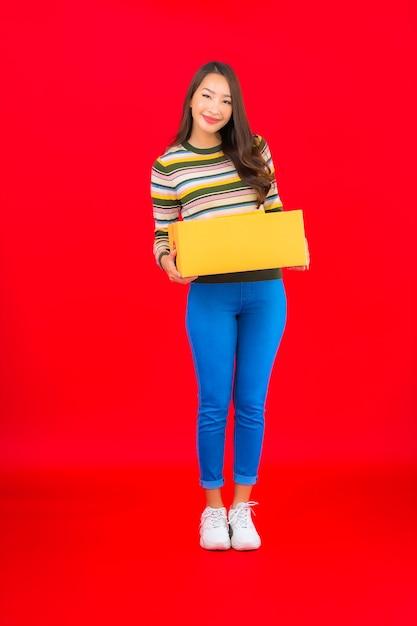 Retrato de uma bela jovem asiática com caixa de pacote na parede vermelha isolada Foto gratuita